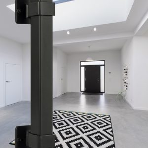 Spacious, bright, white hall with black front door and window in the ceiling